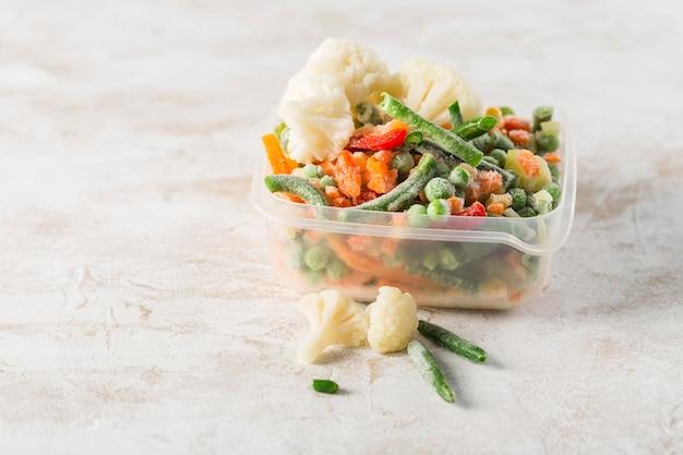 Vegetales congelados. mezcla de verduras, judías verdes y coliflor en un recipiente de plástico para congelar sobre un fondo claro.
