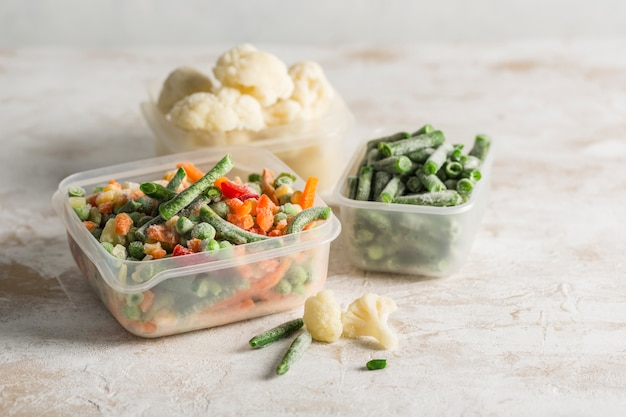 Vegetales congelados. mezcla de verduras, judías verdes y coliflor en varios recipientes de plástico para congelar sobre un fondo claro.