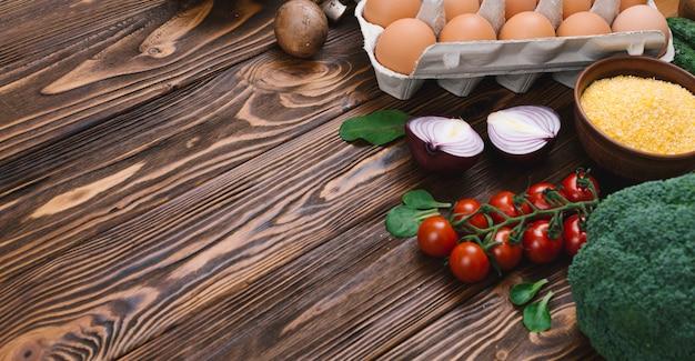 Vegetales frescos; huevo y bol de polenta sobre mesa de madera.
