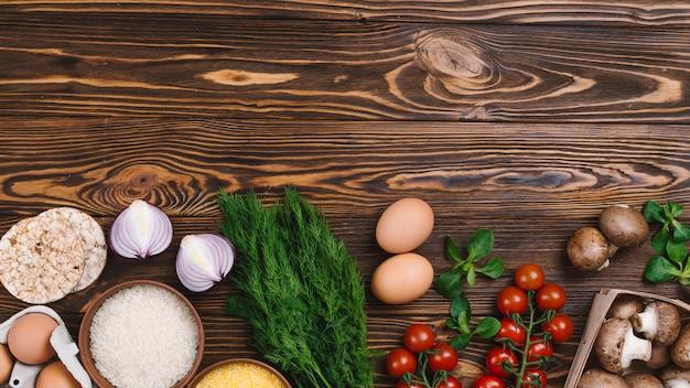 Vegetales frescos; huevos y granos de arroz y pastel de arroz inflado sobre mesa de madera