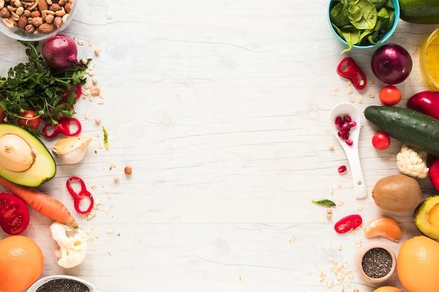 Vegetales frescos; ingredientes y frutas dispuestas en mesa de madera blanca.