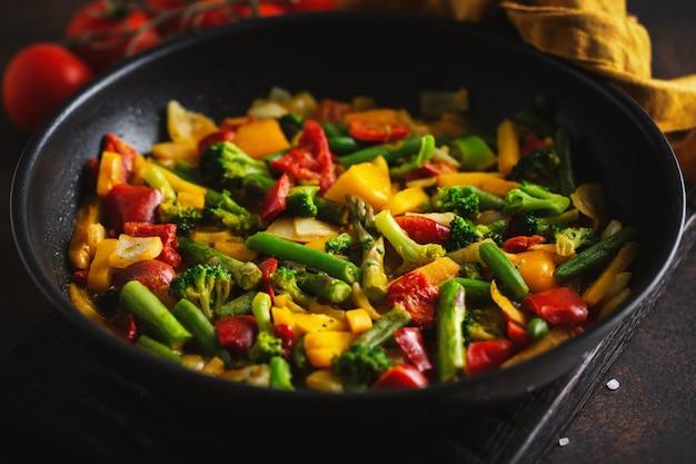 Vegetales fritos con salsa en sartén