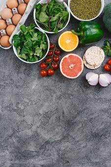 Vegetales de hoja; fruta cítrica; huevos; pastel de arroz inflado y frijol mungo sobre fondo de hormigón