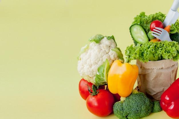 Vegetales orgánicos brócoli pepinos pimientos manzanas en papel marrón bolsa de supermercado kraft en amarillo. dieta saludable fibra dietética vegana libre de plástico. banner de cartel