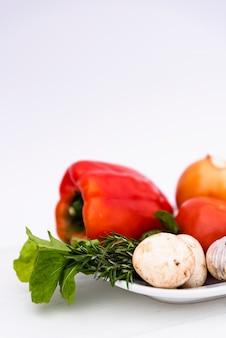 Vegetales orgánicos frescos en bandeja blanca sobre fondo blanco.