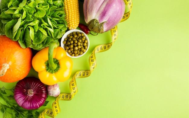 Vegetales saludables llenos de vitaminas sobre fondo verde