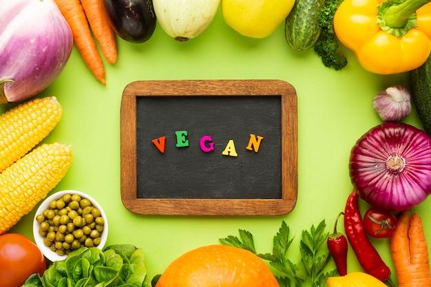 Vegetales sobre fondo verde con letras veganas