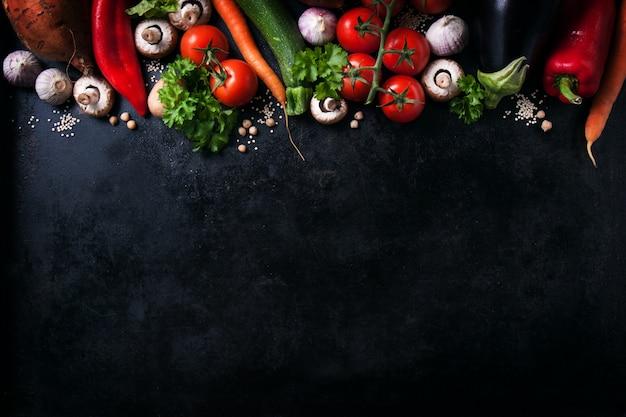 Vegetales varios sobre una mesa negra con espacio para un mensaje