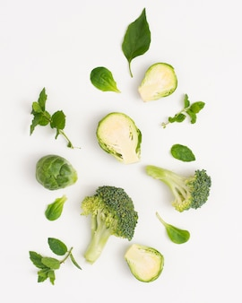 Vegetales verdes orgánicos sobre fondo blanco.