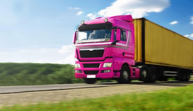 Vehículo camión rosa con contenedor en la carretera y cielo azul con nubes