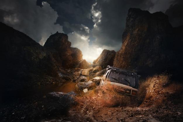Vehículo todoterreno 4x4 saliendo de un peligro de agujero de barro, salpicaduras de barro y agua en carreras off-road en carretera de montaña.