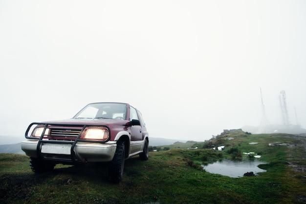 Vehículo todoterreno en una montaña neblinosa temprano en la mañana