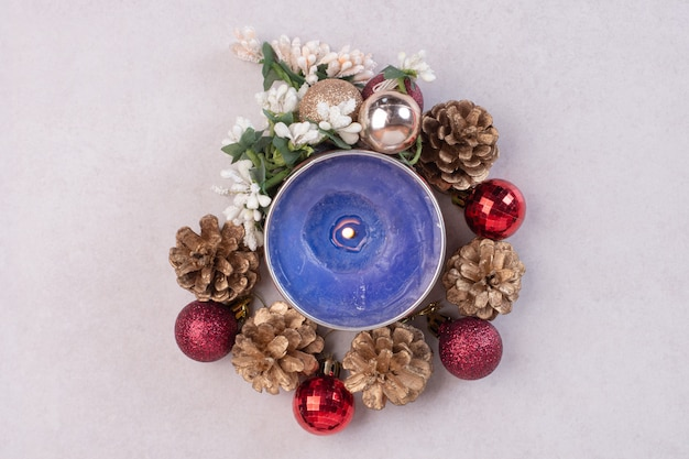 Vela azul con bolas navideñas y piñas