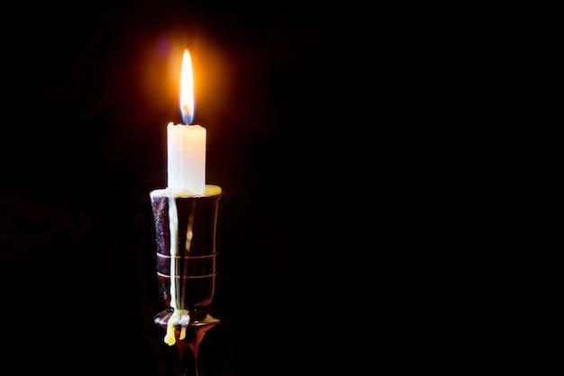Una vela brillaba intensamente en el candelabro. vela en un fondo negro aislado. espacio libre