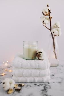 Vela en candelabro con servilletas apiladas cerca de ramitas de algodón y equipos de iluminación en superficie de mármol
