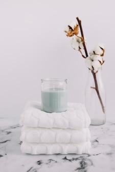 Vela en candelabro sobre servilletas blancas apiladas cerca de una ramita de algodón en una botella