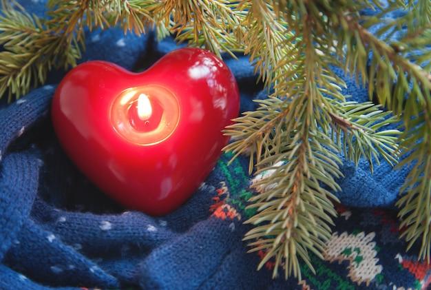 Vela corazón con luz debajo de la rama de un árbol de navidad