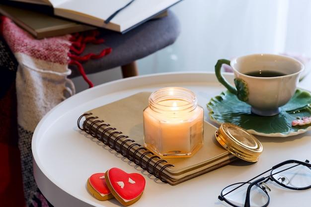 Una vela con un cuaderno, una taza de té en una mesa con una silla, una tela escocesa y un libro. interior de la casa