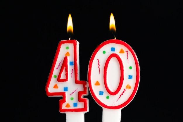 Vela de cumpleaños ardiente colorida sobre fondo oscuro