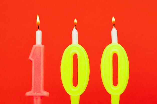 Vela de cumpleaños ardiente colorida sobre fondo rojo