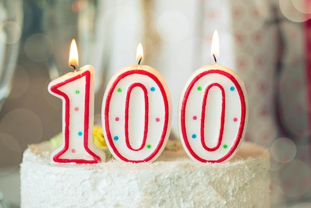 Vela de cumpleaños como número cien en la parte superior de la torta dulce en la mesa, 100 cumpleaños