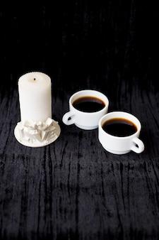 Vela y dos tazas de café sobre un fondo negro