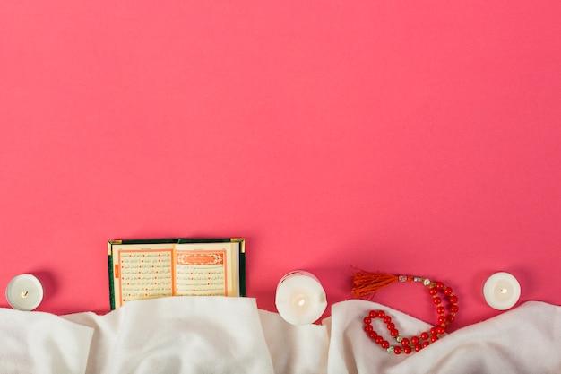 Vela encendida kuran islámico; cuentas de oración con ropa blanca contra el fondo rojo