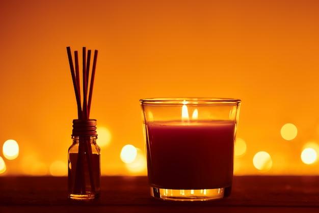 Vela encendida con palos de aroma en una botella de vidrio contra luces doradas borrosas en la oscuridad