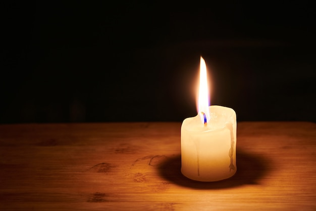 Vela encendida sobre la mesa en la noche oscura