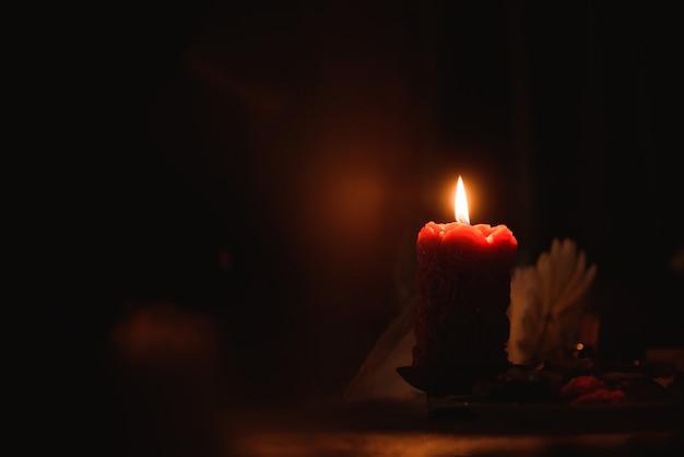 La vela está encendida sobre la mesa en la oscuridad.