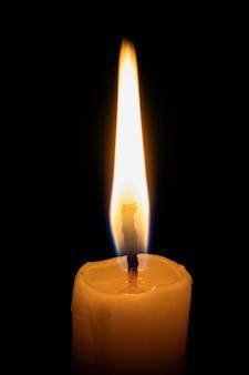 Una vela encendida solitaria en la oscuridad