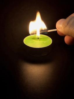 La vela se enciende de un fósforo en una mesa negra