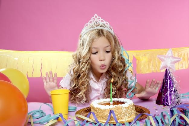 Vela feliz de la torta de la pequeña muchacha que sopla rubia en una fiesta de cumpleaños