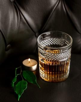 Una vela, hojas y un vaso de whisky.