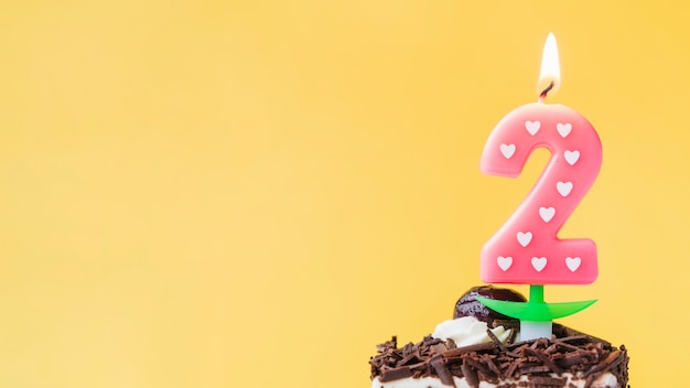 Vela iluminada de dos años en rebanada de pastel sobre fondo amarillo
