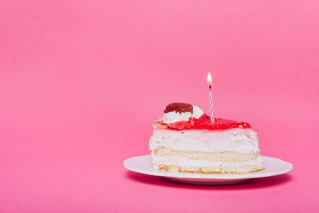 Vela iluminada en rebanada de pastel de cumpleaños con fondo rosa