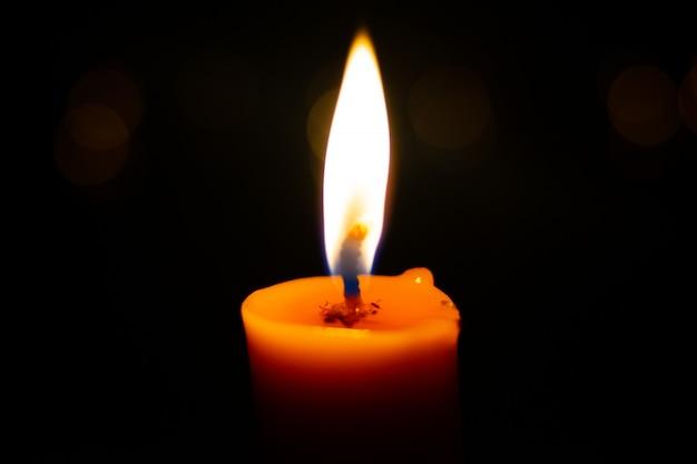 Una vela ligera encendida brillantemente en el fondo negro