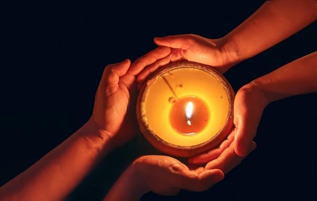 Vela en las manos bendiciendo juntos