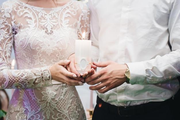 Vela en manos de los recién casados. tradición de encendido del hogar familiar el día de la boda