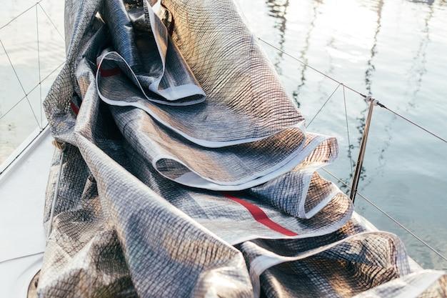 Vela mayor o spinnaker depositado y plegado en la cubierta de un velero o yate de lujo profesional, atracado en un patio o puerto deportivo