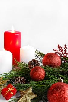 Vela de navidad, ramas de pino de abeto y diseño de adornos navideños en una calle de año nuevo