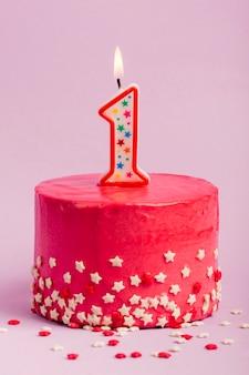 La vela número uno encendida en la torta roja con estrella asperja contra el fondo púrpura