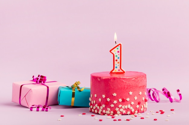 La vela número uno en el pastel rojo con estrellas salpica; cajas de regalo y serpentinas sobre fondo rosa
