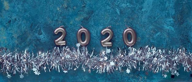 Vela números 2020 y brillante guirnalda de navidad brillante con luces y pequeñas estrellas en azul oscuro con textura, composición panorámica.