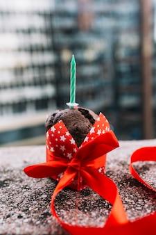 Vela en pastel decorado con cinta roja sobre fondo de hormigón