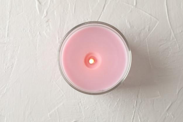 Vela rosa en frasco de vidrio en blanco, vista superior