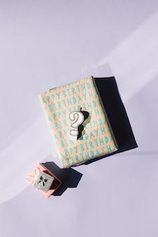 Vela del signo de interrogación en las cajas de regalo envueltas aisladas sobre fondo blanco