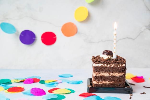 Vela sobre la rebanada de pastel y confeti en la mesa