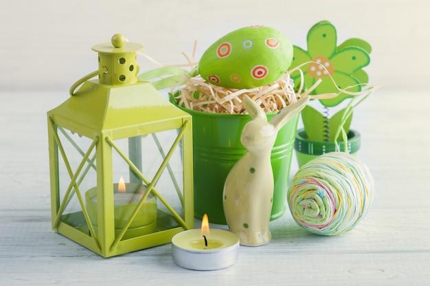Vela verde, conejo de juguete, vela y huevos.