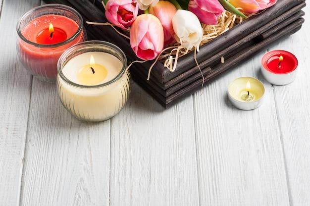 Velas aromáticas amarillas y rosadas con tulipanes